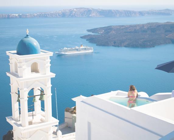 Women in luxury hotel pool overlooking beautiful Sea of Crete in Santorini, Greece on leisure vacation